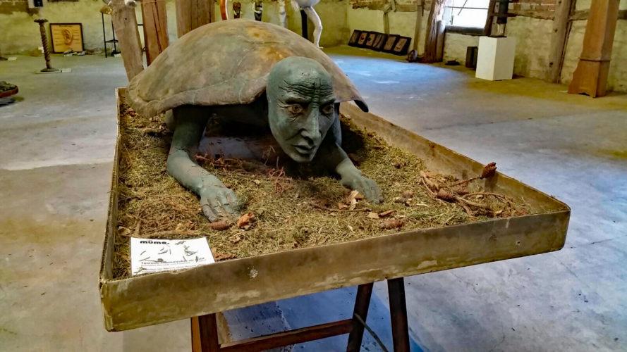 Abbildung: Skulptur, einen Schildkrötenmenschen darstellend.
